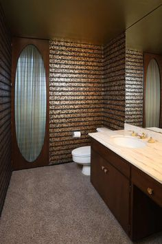 Flocked metallic wallpaper -- with gold foil on the ceiling. Mel Brown built the door with the oval (oval matches the wallpaper pattern) to cover the jalousie windows.