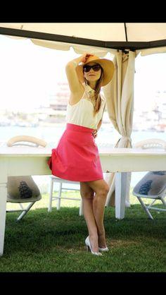 Blusa branca com detalhes em renda e saia de couro rosa.