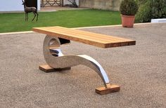 Sculptural metal bench by Chris Bose. Polished steel and oak. Bespoke modern garden seating made to order.