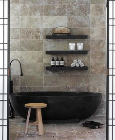 Black tub and shelves, beige marble tile in this luxe bathroom. Even the bathroom toiletries look beautiful