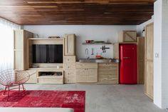 """Para organizar os espaços e as funções de uso social no duplex com apenas 36 m², o arquiteto Alan Chu imaginou um sistema de caixotes inspirado nos """"pallets"""". São essas caixas que """"estocam"""" os equipamentos da residência e dão forma à despensa, à cozinha e à estante para TV, CDs, e outros elementos típicos de uma sala de estar. A marcenaria para o AP 1.211 é da Art Mad"""