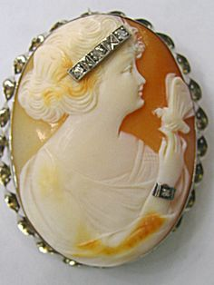 The carving is of a lady in profile wearing a diamond headband and diamond bracelet. The cameo has been framed in a gold twist frame made of 14kt white gold. Circa late 1800's.