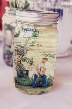 *Photo by Kelsey Jean Photography*   Photo centerpieces = Mason jar + photo + vegetable oil......total cost of $3 per jar!
