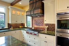 The leather-like finish of the range hood with wrought iron nailhead trim adds immediate intrigue to this cozy kitchen design. Above the stove top, a framed diamond pattern accent panel decorates the dark subway tile backsplash that separates the built in white cabinets from the green marble countertop.