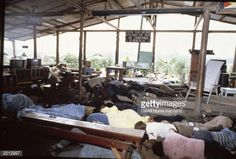 Dead bodies lie in the compound of the People's Temple cult November 18, 1978 in Jonestown, Guyana after over 900 members of the cult, led by Reverend Jim Jones, died from drinking cyanide-laced Kool Aid; they were victims of the largest mass suicide in modern history. In the background, above Jim Jones's chair, a sign from the rafters reads 'those who do not remember the past are condemned to repeat it.'