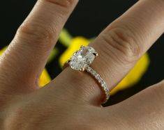 Ladies engagement ring features oval cut forever brilliant moissanite center and natural brilliant cut diamonds styled in 14k rose gold.