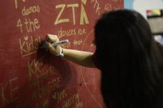"""Dancers take time to write on the """"Why I Dance"""" wall"""