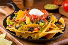 a plate of delicious tortilla nachos with melted cheese sauce ground beef jalapeno peppers red onion green onions tomato black olives salsa and sour cream with guacamole dip. Tortilla Chips, Beef Nachos, Nachos Loaded, Cheesy Nachos, Mexican Dishes, Mexican Food Recipes, Ethnic Recipes, Nachos Mexicanos, Gourmet