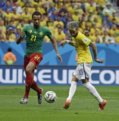 Brazil beats Cameroon 4-1, reaches 2nd round - Brazil's Neymar kicks the ball past Cameroon's Joel Matip to score his side's first goal during the group A World Cup soccer match between Cameroon and Brazil at the Estadio Nacional in Brasilia, Brazil, Monday, June 23, 2014. (AP Photo/Natacha Pisarenko)
