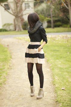 Falda de color blanca con rayas negras y jersey de punto negro con cuello grueso, medias negras y botines blancos, simple pero perfecto.