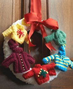 Open your heart and your home this holiday season with this festive knitted wreath! Adorned with miniature knit sweaters, this wintery door decor item is a must-knit!