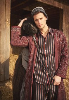 Garrett Neff works a boho lord of the farmhouse vibe while Zephyr the llama stays warm in cashmere from Michael Kors.