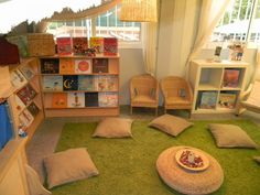 I like the large space this reading area has. I also like how chairs and pillows are providing for seating in the area, along with three shelves for books.
