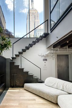 A blackened steel staircase by Delform leads to the upper level. A tall glass clerestory frames views of the Empire State Building and reinforces the indoor/outdoor motif.