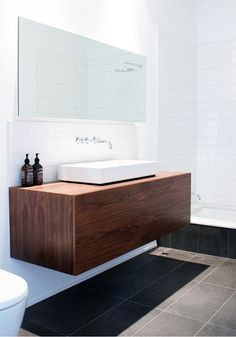 wooden vanity + white straight lay tiles behind taps