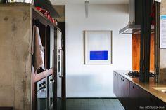 Cozinha integrada tem móveis com estrutura em concreto e piso de ladrilho hidráulico.