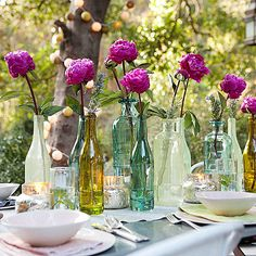 For a garden party to remember, bring blooms to the table with the help of glass bottles. Tall flowers with long stems, such as peonies, are perfect for this arrangement. Low candles are an ideal contrast to the floral centerpiece. For added festivity, string globe lights from branch to branch.