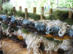 Weaving on a peg loom with natural wool and wool roving.