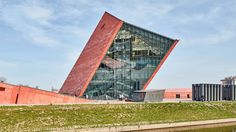 A distorted geometric tower wrapped in red concrete panels and glazing contains the entrance to this second world war museum in the Polish city of Gdansk.