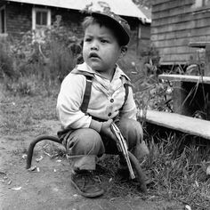 A little boy seated on a metal bar with a toy pistol. Undated, Canada