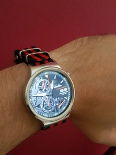 huawei smartwatch on wrist. huawei smart watch with red and black nato strap. smartwatch on wrist