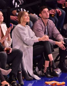 Sitting court-side at a New York Knicks basketball game wearing a taupe trench coat, black leggings and sky-high stilettos.