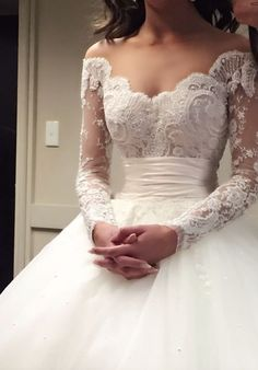 Elegantly unique off-the-shoulder embroidered long-sleeve wedding dress with empire waistline; Featured Dress: Steven Khalil