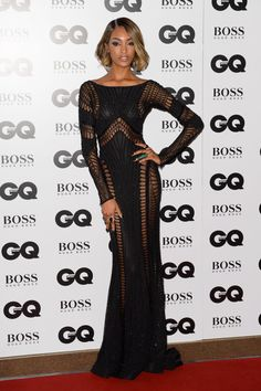 Supermodel Jourdan Dunn brings her super-good looks to the red carpet in an elegant yet sexy black dress. The form-fitting gown flatters her fit figure and features several cutouts.