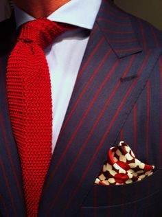 navy and red pinstripe suit paired with red knitted tie