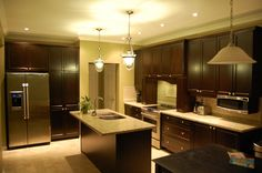 espresso cabinets, granite counters. love the pendant lights
