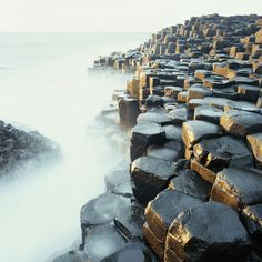 The Giant's Causeway, Northern Ireland (in mist). Formed by volcanic activity the stones are made of basalt and are of geometric shapes. Land Art, Travel Pictures, Travel Photos, Basalt Columns, Europe Travel Guide, Beach Landscape, Dream Vacations, Places To See, Travel Inspiration