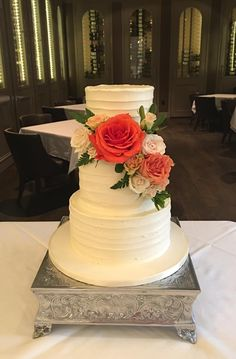 3-tiered buttercream finish wedding cake, decorated with fresh roses and greenery.
