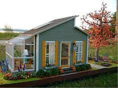 Cute little house/shed with greenhouse. Love the colors!: