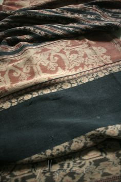 """Quite old ei worapi or non ceremonial sarong from Savu in faded morinda and indigo. Still, influenced by European floral design for the main pattern but executed on morinda background instead of dark indigo. Both of medi ae and ro'a bands done in light indigo (or maybe darker indigo but already faded). The """"bunga wurumada"""" stitches has already tear off of the sarong and only left a little part remain. From Savu - East Nusa Tenggara"""