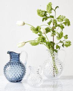 Glaskaraff tillverkad för hand i ett klassiskt glasbruk. Kannan har ett fantastiskt organiskt mönster av bubblor blåsta i glaset. Finns i flera färger som alla är vackra var för sig eller tillsammans i grupp. Passar även fint som vas. Finns i två olika storlekar. FÄRGER: Clear Glass, Ocean Blue, Water Green och Amber MÅTT: H: 25 cm Volym: 2,2 l. Mini H: 15 cm Volym: 6,5 dl. MATERIAL: Glas. Tål maskindisk.