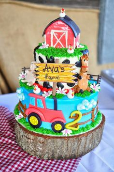 Two year old Ava's layered farm cake with barn, cow print, fence & tractor on tree slice for stand