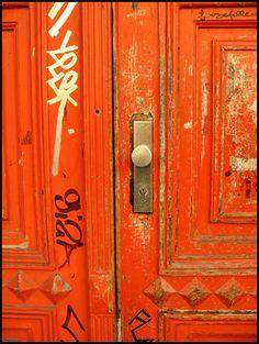 Orange doors with graffiti.@Amelia Stone Coquis via Chantal Lang
