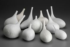 "Suzanne Stumpf: Whale Sounds, 2007, 8"" h x 29"" w x 20""d, porcelain or porcelain paperclay; handbuilt with thrown necks; reduction fired to cone 10.Whale Sounds is a multi-component, interactive sculptures. The shapes were inspired by listening to a recording of whales in which the whales' calls ballooned rapidly and diminished into fine, thin, high endings. (Although some of the objects can elicit tones when blown, this was not my intention.)"
