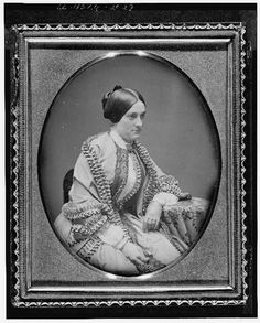 "[Ann Minerva ""Nannie"" Rodgers Macomb, three-quarter length portrait, facing right, seated in chair with arm resting on table with tablecloth]"