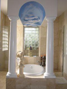 Bathtub with elegant pillars ceiling mural of sky