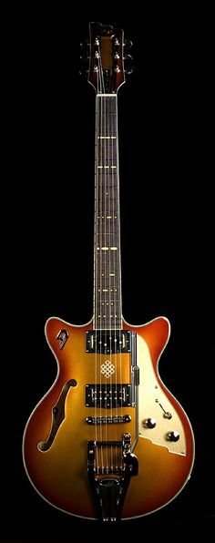 Duesenberg Alliance Joe Walsh Signature Guitar. Features – Gold Burst Finish – Laminated Arched Spruce Top & laminated Maple Back and Sides – American Hard Rock Maple Neck – Indian Rosewood Fretboard – Duesenberg HSC Single Twin Neck Pickup – Little Toaster Humbucker Pickup – Dual Duesenberg D-Tron Humbucker Pickups – Duesenberg Bridge with Steel Saddles – Duesenberg Radiator Tremolo with Gold Grille – Deluxe Tuning Machines. 2 of 2