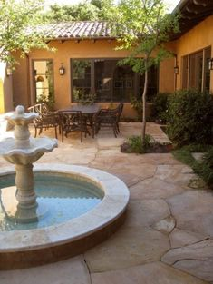 An enchanting hacienda courtyard. The neatly laid flagstone recedes just enough to allow for a tree to be tucked into the space. Love the warm color on the walls.