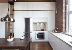 A floor-to-ceiling wall unit accommodates a fridge, stove, oven, and convertible custom cabinetry. The pendant light is from the Multi Luminaire showroom in Pointe Claire, Quebec; the appliances are from Bosch and Miele.
