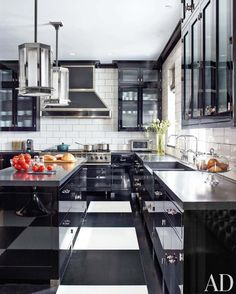 The kitchen of a Manhattan duplex with pendant lights and cabinets lacquered in black. Photographed by Eric Pasiecki by roomporn