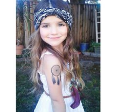 Adorable little girl with a dream catcher tattoo and a blue bandana in her hair
