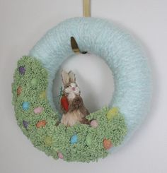 Its like an Easter basket for your door! 12-inch wreath with pale blue yarn base, brown rabbit, felt grass and shimmery Easter eggs. This