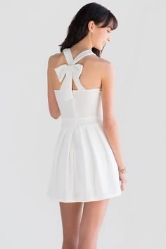 Ava Bow Back Dress features a halter silhouette with a blooming bow in the back & comes in a choice of white or black. Perfect spring/summer date night outfit!