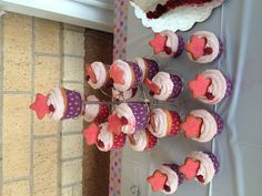 American Girl theme cupcakes. Pink lemonade cupcakes with raspberry buttercream frosting topped with a little star shaped raspberry cookie and a single raspberry.