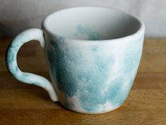 A lovely pair of turquoise and white mugs, perfect for drinking from while gazing into a sunset/your lovers eyes/your kitchen (yknow, whatever makes you feel cosy.) These mugs were thrown on my pottery wheel, trimmed and fired and then glazed with Scarvas matte white and turquoise blue. I used a slightly different technique on these two, I added a little washing up liquid to the blue glaze and then blew the bubbles onto the surface of the mugs. Its diffused and mixed nicely with th...