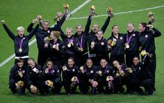 The U.S. women's soccer team celebrates with their gold medal after winning the final game against Japan.